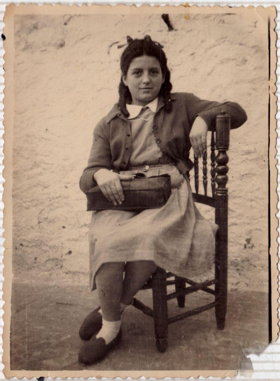 Isabel Gallart molt joveneta, amb espectaculars tirabuixons  i la bossa d'escola.
