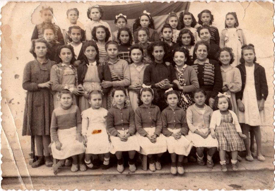 Potser un parell d'anys després, les més majors ja havien acabat l'escola. La foto ha de ser aproximadament de l'any 48. La mestra és Doña Rosario, tia de la propietària d'estes fotos.