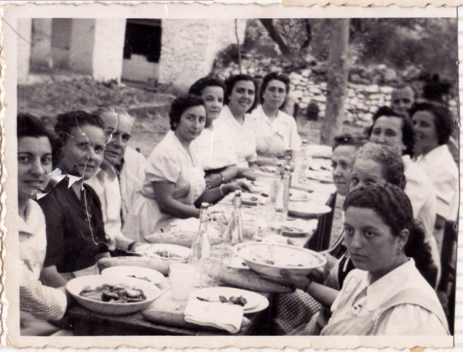 Superant la foto anterior, en esta imatge tenim un mestre més. D'esquerra a dreta, reconeixem, en tercer lloc, a Don Juan Ros (un mestre que, cosa rara en aquell temps, no pegava als xiquets), Pilar Ferrero, Doña Claudia, Doña Adoración i la germana, i darrere d'Isabel a sa tia Doña Rosario. Estan dinant a l'Ermita.