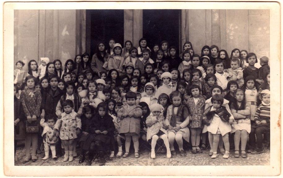 Xiquetes a la porta de l'església, les de davant assegudes en catrets. MOltes porten el cap tapat, com corresponia a les dones de l'època. Pels cabellsi els vestits, pot ser de principi dels anys 30.