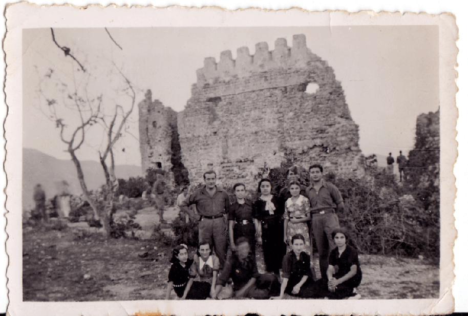 """La imatge mostra un grup de soldats i de xiques del poble poc després de l'entrada de l'exèrcit nacional en Artana. Com es sap, la 4ª Divisió de Navarra va entrar a Artana pel Castell el 4 de juliol de 1938, i va causar un gran entusiasme en part de la població. Fruit d'aquest entusiasme fou l'amistat entre alguns soldats i famílies del poble, que es van prolongar durant anys després de la guerra. En la fotografia s'hi reconeixen les xiques del poble: d'esquerra a dreta i de dalt avall, Felicidad de Coloma, Doloretes de Clàudia, Genoveva, Lolita el Rosso, Marí Roqueta, Doloretes de Roqueta i Marí Racó (la primera i la penúltima vestides de falangistes). Quant als soldats, algunes de les xiques presents n'identifiquen dos: el primer per l'esquerra era intendent i l'anomenaven """"el Carnisser"""". I el de més a la dreta es deia Jaime, era un xic de Barcelona que, una vegada acabada la guerra, va tornar a Artana en nombroses ocasions, de vegades acompanyat per sa mare. Foto cedida per Marí Racó."""