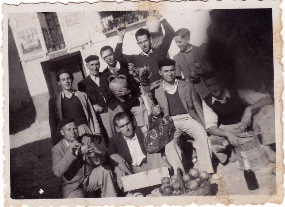 Es pot imaginar que la colla d'amics estaven preparant alguna celebració. Es tardor, temps de mangranes, i posen davant de la font, a la plaça Major. Cap a l'any 50.