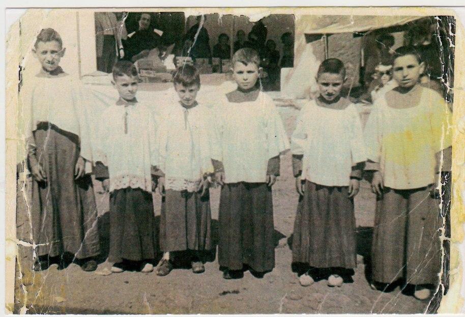 Una imatge de sis acòlits o escolanets a l'Ermita el dia de Santa Cristina cap a l'any 1948 ó 49. Darrere es poden veure les parades de la Fira. Els xiquets són, d'esquerra a dreta, Vicente Herrero ('Vicente Peneque'), un desconegut, Bernardo, Miguel de Panxut, Juanito Calo (a qui debem, indirectament, esta imatge) i José Serreta. Tots els xiquets porten sotana, i damunt, els cinc de la dreta porten el roquet o sobrepellís, un ornament litúrgic que solia ser de lli blanc i estar vorejat d'una àmplia punta brodada (com la del segon i tercer per l'esquerra). El primer va revestit a la manera dels sagristans, és a dir, amb una tela ampla sense mànegues, amb un únic forat per al cap. Si sabem que el major (Vicente) tenia onze o dotze anys, els més xicotets no en tindran molt més de huit o nou.