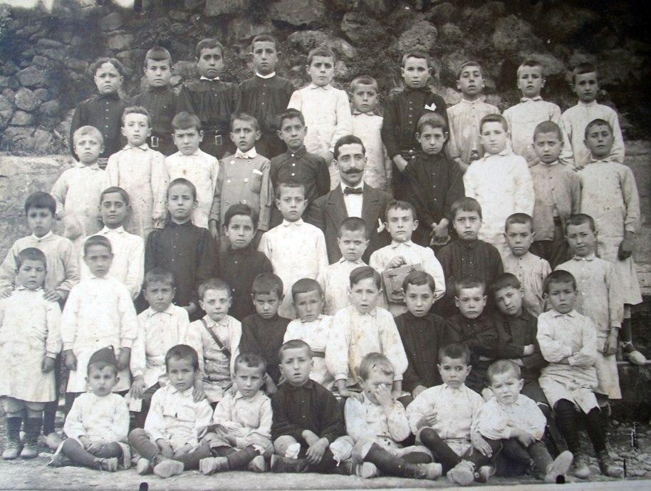 """El company Jordi López Vilar ens envia esta foto en molt bona qualitat d'un grup d'escolars. Un d'ells és el seu avi, pel que dedueix que la instantània és del voltant de 1910. Ahí estaran també alguns dels nostres pares i avis (possiblement els dos iaios de qui redacta estes línies), però són mals d'identificar. Tampoc no hem sabut trobar on es va fer la foto, amb eixes grasades altes; potser ha canviat al llarg del segle que ens separa de la imatge. És curiós veure les llargues bates blanques que portaven els xiquets com a uniforme, herència de les antigues escoles religioses. Alguns dels alumnes no portaven la bata, de vegades per desídia dels pares (perquè la formació no estava ben valorada) o perquè no podien pagar-se-la. De qualsevol manera, els que no portaven uniforme anaven igualment """"uniformats"""" amb brusa negra. A més a més, els xiquets van quasi tots pelats, que era la forma més senzilla d'evitar paràsits. El mestre va a la moda del temps: llargs bigotis i llacet al coll, amb una jaqueta molt formal. Aleshores els mestres estaven particularment mal pagats (es parlava de """"passar més fam que un mestre d'escola""""), i no era estrany que a l'ensenyament es dedicara gent que no podia treballar en altres oficis més corrents. És a dir, que qui no servia per a treballar se n'anava a l'estudi, de vegades amb els frares, que resultava més barat."""