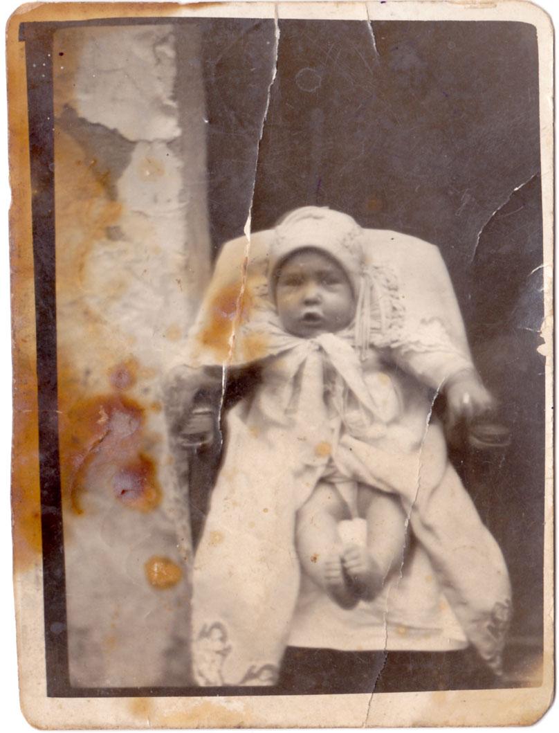 Un altre infant de bolquers, ara molt mudat i assegut a la porta de casa. Possiblement també dels anys 20-30.