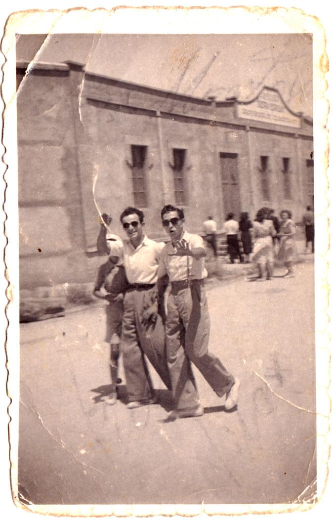 Dos galans passejant per la carretera al migdia d'un diumenge o festiu.