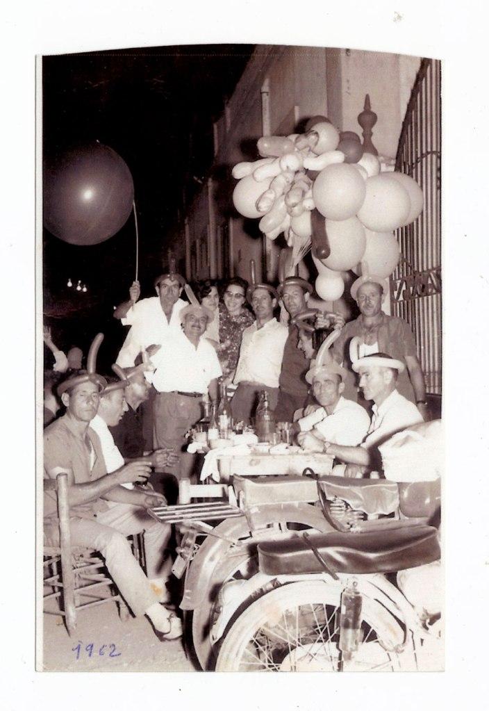 La més recent és d'un sopar de la Penya Imperio el diumenge 2 de setembre de 1962, en les festes patronals de Sant Joan. Els joves tenien 40 ó 41 anys. En primer plànol tenim dos motos, que en aquells anys era el mitjà de transport dels treballadors, substituint les bicicletes. Sorprén veure aquell pom de bufes tan originals, grans, de formes estranyes o lligades al cap. Es troben a la carretera, davant mateix de l'edifici de l'Almàssera, on es feien els balls en aquell temps, quan encara no hi havia un trànsit continu de cotxes –després es traslladaria dins de la replaça de l'Almàssera. Al fons es veuen peretes de la llum i algun tipus d'ornament de festa. Es veuen barrals de vi rodant i botelles de licor. Taula de fusta i cadires amb cul de boga. Fan cara d'estar passant-lo molt bé, segur que aquelles no tenien res que envejar a les festes d'ara, començant perquè la gent es concentrava molt més i hi havia més concòrdia entre els veïns del poble. Darrere, amb la bufa més grossa, Juanito Blai, i davant d'ell Deogracias Montoliu. La xica amb ulleres és Rosarito la dona de Blasco, amb la seua cunyada; Blasito Àlvaro, Juanito Manyà, Ramonet el Llumero; l'esmentat Blasco, i davant, asseguts a la dreta, Andreu i Juanito Puça. En front tenen a José Sastre, un amic de Deogracias de Castelló, i a Patrício.