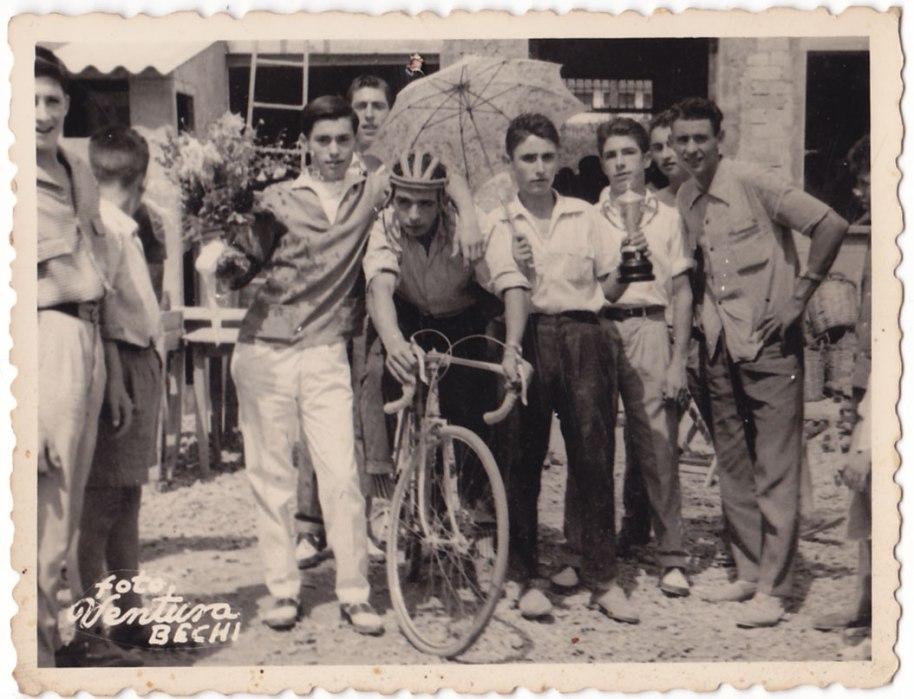 Una  carrera ciclista el diumenge 30 d'agost de 1959, festes de Sant Joan. Darrere veiem obres a la carretera. Ja havia començat la urbanització. Els retratats són José Pansa i darrere pareix Juanito Pau. No hem reconegut el ciclista, però a la dreta té a Juanito Calo, Antonio el Pellero i Peret el de Vilavella