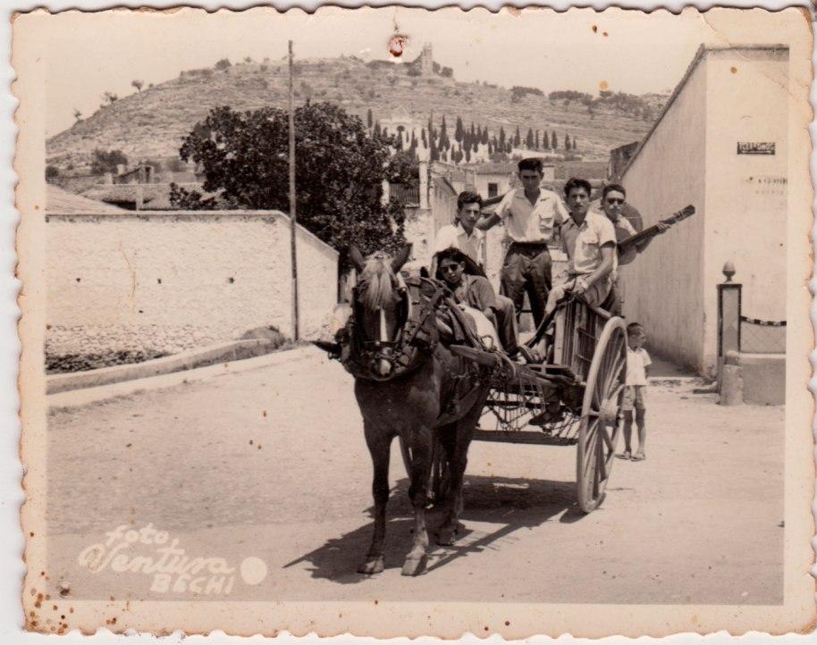 A cavall d'un carro, a migdia, amb sombreros mexicans i guitarres, possiblement anant de paella a l'Ermita. Eixen del poble pel carrer Sant Ramon. A la dreta es veu l'abeurador molt adornat que després es llevaria per posar-lo a l'altre costat de carrer (i on Roia va trencar la Reva). Els joves són, d'esquerra a dreta, Escaleta, Juanito Corina, Vicente Pla, un desconegut, i davant de tots Joaquín de Músic.