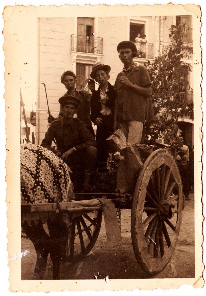 Quatre joves disfressats en un carro molt adornat, segurament en algun tipus de cavalcada. Són, d'esquerra a dreta, un desconegut, Vicente Vilara, Eladio i, ajupit, Vicente Pla.