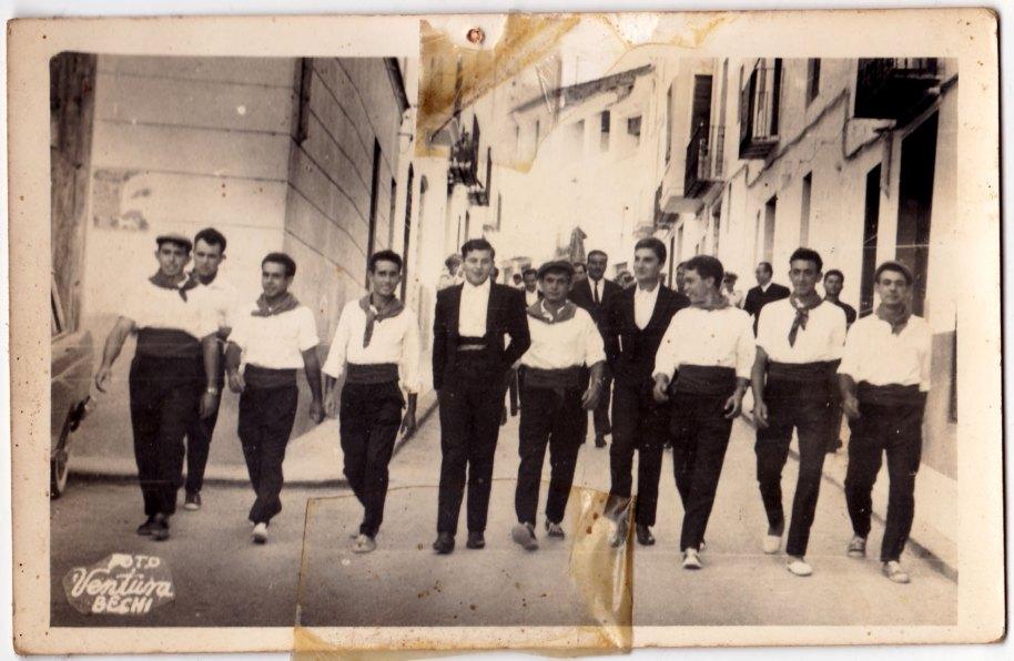 La resta de les imatges són de la correguda de bous celebrada el divendres 30 d'agost de 1963, de nou a les festes de Sant Joan, en una plaça portàtil. Ja vam donar detalls de la correguda en dos fotos publicades, respectivament, a les col·leccións GENERAL 2, i JOSÉ RICO 2. Ací estan pegant la volta al poble amb la banda de música. Els mossos són, començant per l'esquerra, Francisco Roc, Miguel de Panxut, Cantos, Eladio, Bonet entre dos toreros, i Felip entre dos desconeguts