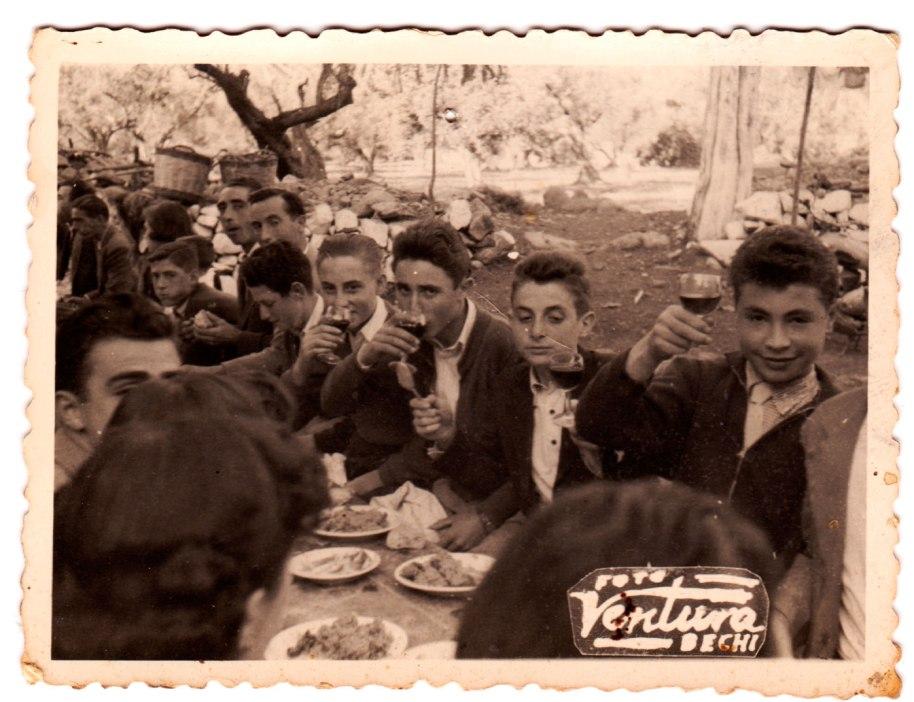 Foto Ventura, Betxí, datada darrere el divendres un de novembre de 1957, dia de Tots Sants. Estan de paella a l'Ermita i els xiquets no se priven de brindar amb vi. De dreta a esquerra són Vicente Casota, Benjamín de Cabedo, Juanito Calo, Ángel, José Manzana i Pasqualet de Baleso.