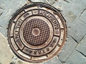 Tapa d'una claveguera que indica l'any que es va fer l'obra de les aigües potables al poble.